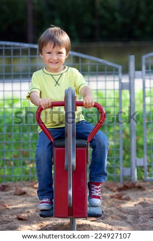 Cute boy on the playground, having fun, summertime