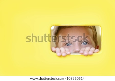 Cute boy peeping through the hole in wooden wall - stock photo