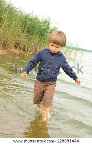 Cute boy playing and having fun on the beach