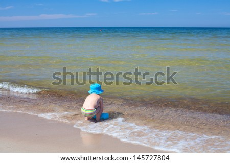 cute boy playing at the beach