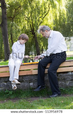 Cute boy playing chess with his grandfather in a park