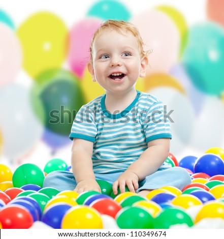 Cute boy playing colorful balls - stock photo