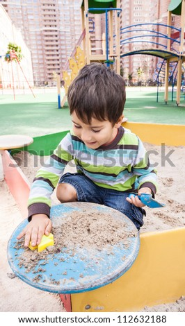 Cute boy playing in sandbox with a sand toys
