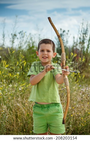 Cute boy playing outdoors with wooden bow and arrows - stock photo