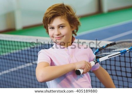 Cute boy playing tennis and posing in court indoor