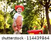 cute boy playing with a red wheelbarrow in summer park - stock photo