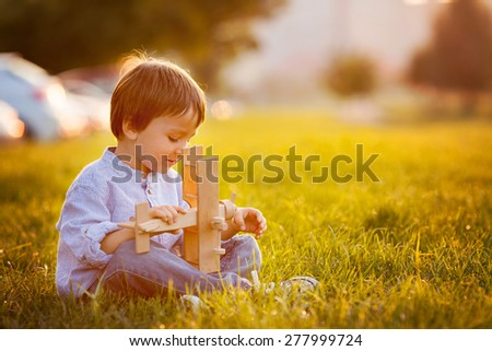 Cute boy, playing with airplane on sunset in the park, smiling - stock photo