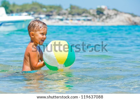 Cute boy playing with ball and swimming in the transparent sea - stock photo