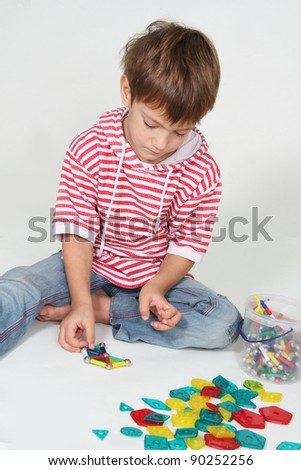 cute boy playing with colorful details studio shot