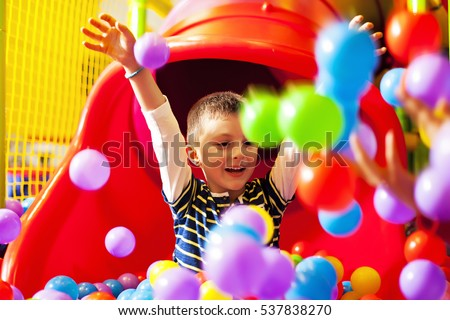 Cute boy playing with plastic balls in an indoor playground
