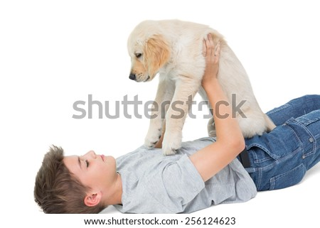 Cute boy playing with puppy over white background