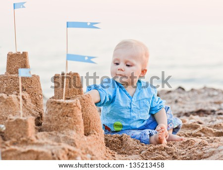 cute boy playing with sand on beach - stock photo