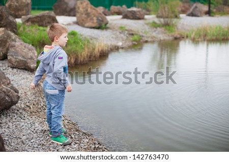 Cute boy playing with stones outdoors - stock photo
