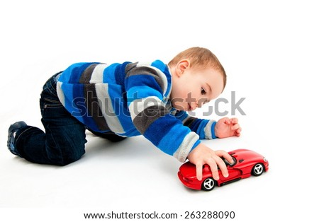 Cute boy playing with toy car - stock photo