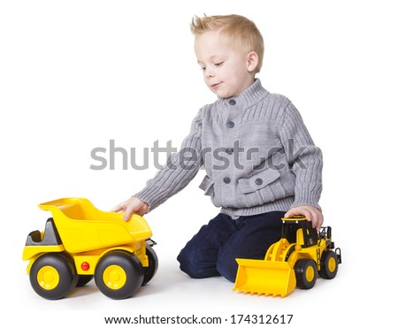 Cute Boy playing with toy trucks