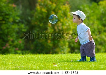 Cute boy plays with a giant bubble outside in the park - stock photo
