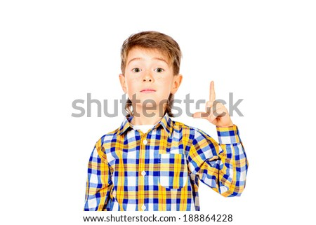 Cute boy raised his index finger to draw attention. Isolated over white. - stock photo