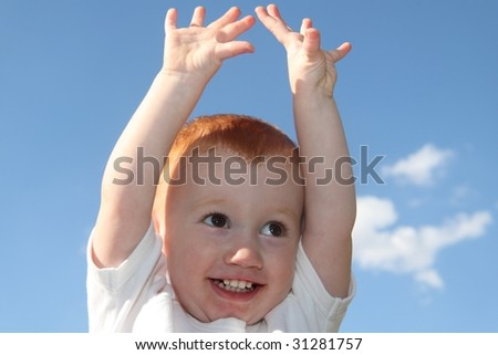 Cute boy reaching for sky