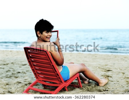 cute boy reads an ebook on chairs by the sea in summer - stock photo