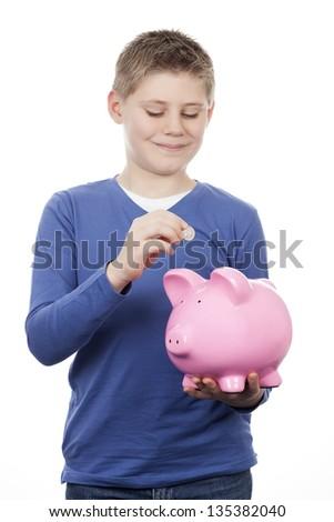 Cute boy saving money in a piggybank - stock photo