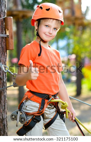 Cute boy shows thumb up with climbing equipment in an adventure park - stock photo