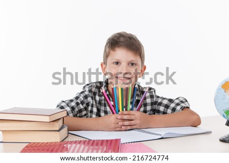 cute boy sitting at table and holding colorful pencils. handsome little schoolboy studying on white background