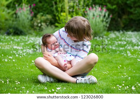 Cute boy sitting in a beautiful summer garden full with flowers holding his newborn sister