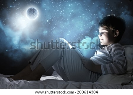 Cute boy sitting in bed and using tablet pc - stock photo