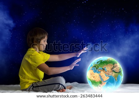 Cute boy sitting in bed holding Earth planet. Elements of this image are furnished by NASA - stock photo