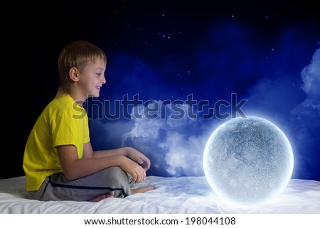 Cute boy sitting in bed with moon planet