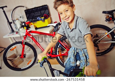 Cute boy sitting on bicycle in garage