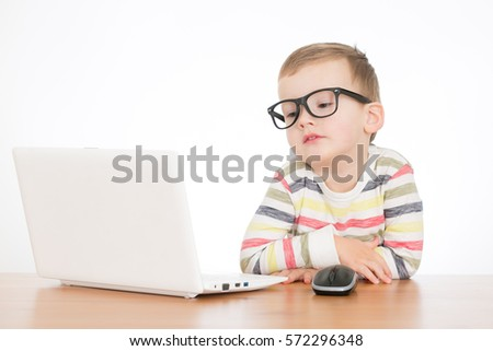 cute  boy sitting on the table with laptop