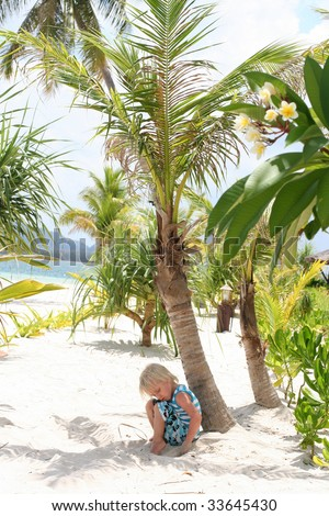 Cute boy sitting on the white sand of tropical paradise - stock photo