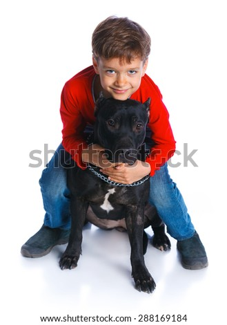 Cute boy sitting with his Pit Bull Terrier smiling at camera on isolated white background