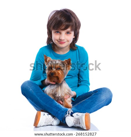 Cute boy sitting with his puppy Yorkshire terrier smiling at camera on white background