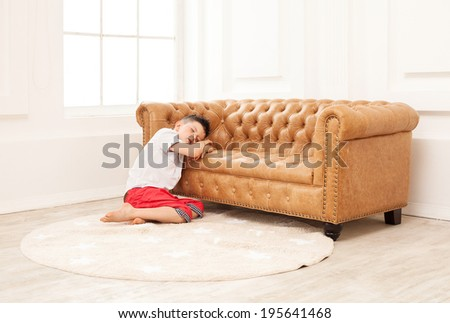 Cute boy sleeping while sitting on floor at couch at home - stock photo