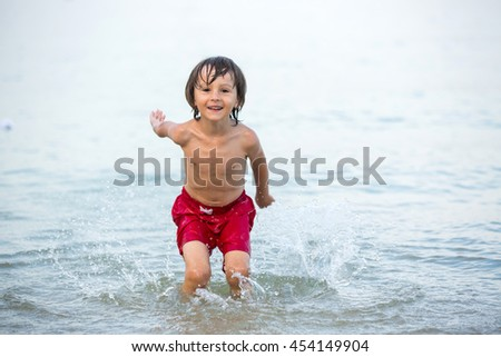 Cute boy, splashing water on the beach, having fun - stock photo