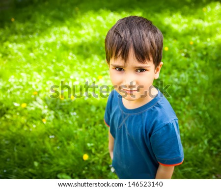 Cute boy standing against green grass background - stock photo