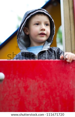 Cute boy standing on top of outdoor playhouse - stock photo