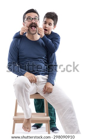 Cute boy surprised to see his father's mustache isolated on white background. - stock photo