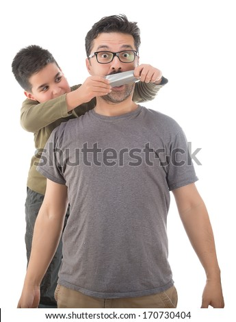 Cute boy tapes his father's mouth with duct tape isolated on white background     - stock photo