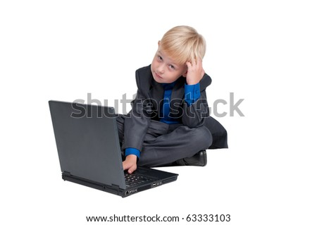 Cute boy thinking over a task on his laptop - stock photo