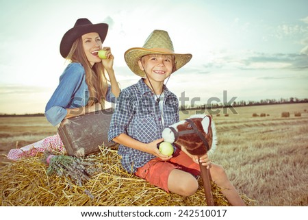 Cute boy traveler feed his toy horse with mother behind him. focus on boy, toned image