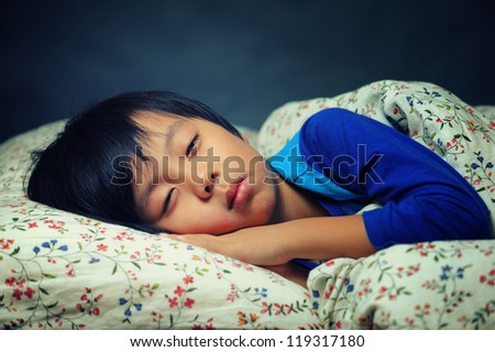 Cute boy trying to fall asleep (eyes slightly opened) - stock photo