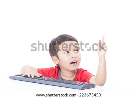 Cute Boy using a keyboard and pointing up - stock photo