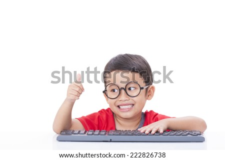 Cute Boy using a keyboard and showing thumb up - stock photo