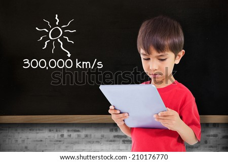 Cute boy using tablet against blackboard on wall