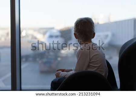 cute boy waiting at the airport and enjoying plane view - stock photo