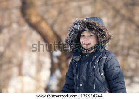 Cute boy walk in the winter park in sunny day - stock photo