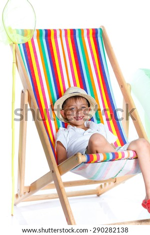 Cute Boy wearing a hat sitting on beach chair. Isolated On White Background. - stock photo